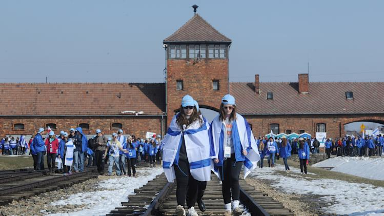 Participants of the March of the Living walk  along rail tracks in the former Nazi Death Camp Auschwitz Birkenau in Oswiecim, Poland, Monday, April 8, 2013. Jews from Israel and around the world took part in the annual March of the Living on the 3km route from Auschwitz to Birkenau Nazi Death Camps, commemorating the Holocaust victims. (AP Photo/Alik Keplicz)