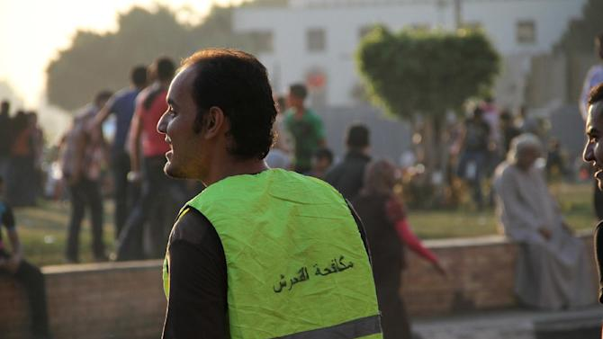A  volunteer wearing a vest printed with the text Anti harassment monitors Cairo's Tahrir Square in this Sunday Oct 28 2012 photo. A group of Egyptians had a mission for this year's Eid al-Adha, Islam's biggest holiday, which began Friday. They wanted to make some effort to stop sexual harassment of women, which in past years has spiked in Cairo during the holiday celebrations with the crowds of rowdy men in the streets. In past years, the Eid has seen major instances of harassment, with crowds of young men groping passing women — so heavily that women had to flee into shops, and for days afterward newspapers decried the mob attacks. (AP Photo/ Mohammed Abu Zeid)