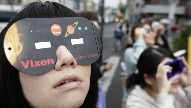 """People watch the annular solar eclipse in Fujisawa, near Tokyo, Monday, May 21, 2012. Millions of Asians watched as a rare """"ring of fire"""" eclipse crossed their skies early Monday. The annular eclipse, in which the moon passes in front of the sun leaving only a golden ring around its edges, was visible to wide areas across the continent.  (AP Photo/Shizuo Kambayashi)"""