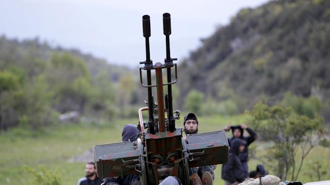 Rebel fighters stand on pick-up truck mounted with anti-aircraft weapon near Jisr al-Shughour, in Idlib countryside, during what they saidwas offensive to take control of town and its surroundings