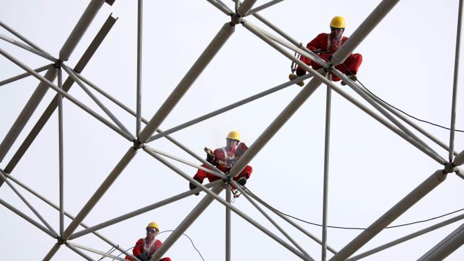 Workers set up scaffolding at a construction site in Huaibei