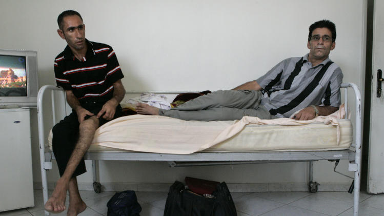 In this Sunday, Aug. 5, 2012 photo, Iranian Kazem Shavori, 40, left, who is suffering from hemophilia, talks about his knee problems, as he sits next to Moslem Kolivand, 33, who is also a hemophiliac, at Iran's Hemophilia Association center, in Tehran, Iran. While medicine and humanitarian supplies are not blocked by the economic embargoes on Iran over its nuclear program, the pressures are clearly evident in nearly every level of Iranian health care. It's a sign of the domino effect of sanctions on everyday life. (AP Photo/Vahid Salemi)