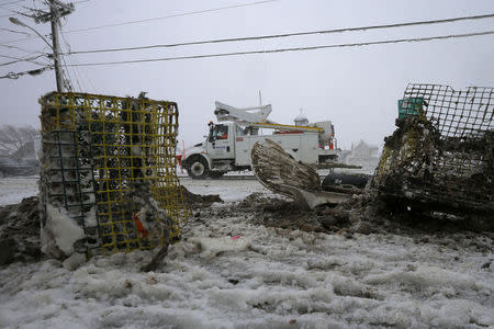 An NStar Electric repair truck sits next to debris, including lobster traps, near the ocean's edge during a winter blizzard in Marshfield