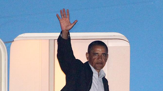 President Barack Obama waves from the door of Air Force One at the Cape Cod Coast Guard Station in Bourne, Mass., after ending his vacation on Martha's Vineyard early, Friday, Aug. 26, 2011. (AP Photo/Stew Milne)