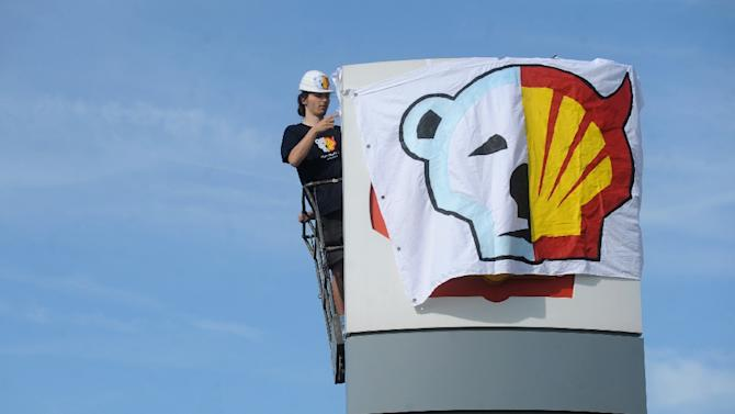 File picture shows a Greenpeace activist covering the Shell logo during a protest against the sailing of an icebreaker for Shell's Arctic oil drilling project in the north of Alaska