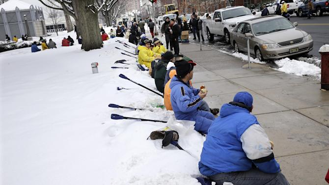"""Workers take a lunch break from shoveling snow near the Statehouse in Tuesday, Feb. 18, 2014, in Trenton, N.J., after a quick-moving storm brought several inches of snow as well as rare """"thundersnow"""" to parts of the winter-weary East Coast. (AP Photo/Mel Evans)"""