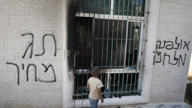 "A Palestinian child stands outside a vandalized mosque in the West Bank town of Jabaa, near Ramallah, Tuesday, June 19, 2012. By July 1, the government has committed to destroying 30 apartments settlers built illegally on privately held Palestinian land. Acts of vandalism against Palestinian property have been expected ahead of that date because radical settlers routinely attack Palestinian targets in retaliation for government settlement policy they oppose. From left to right Hebrew writing reads, ""price tag"" and ""Ulpana war."" (AP Photo/Majdi Mohammed)"