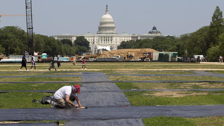 Larry Pellino repairs the site of the AIDS Memorial Quilt display damaged by a powerful storm that swept across the Washington region Friday, at the National Mall in Washington Saturday, June 30, 2012. Organizers of the quilt display are planning to put the exhibit back on Sunday.  Violent storms swept across the eastern U.S., killing at least nine people and knocking out power to hundreds of thousands on a day that temperatures across the region are expected to reach triple-digits.  Officials said about 500,000 people were without power in West Virginia. (AP Photo/Manuel Balce Ceneta)