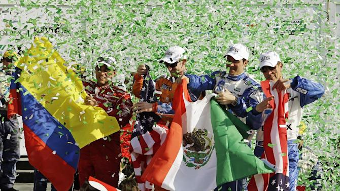 From left, Ganassi Racing team drivers Juan Pablo Montoya, of Colombia, Charlie Kimball, Memo Rojas, of Mexico, and Scott Pruett wave flags as confetti rains down on them after winning the Grand-Am Series Rolex 24 hour auto race at Daytona International Speedway, Sunday, Jan. 27, 2013, in Daytona Beach, Fla. (AP Photo/John Raoux)
