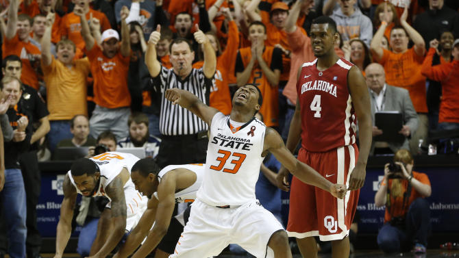 CORRECTS TO OVERTIME, NOT SECOND HALF - Oklahoma State guard Marcus Smart (33) celebrates after blocking a three-point shot attempt by Oklahoma guard Steven Pledger (2) with 18 seconds to go in overtime of an NCAA college basketball game in Stillwater, Okla., Saturday, Feb. 16, 2013. Oklahoma forward Andrew Fitzgerald is at right. Oklahoma State won 84-79. (AP Photo/Sue Ogrocki)