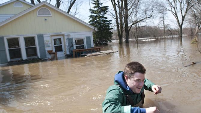 Joe Biggerstaff wades away from his mother's Konkle Drive home on the Grand River north of downtown Grand Rapids, Mich., Sunday, April 21, 2013. The rising Grand River has driven hundreds of people from their homes in several western Michigan communities and was pushing Sunday toward a record high near Grand Rapids. (AP Photo/MLive.com, Chris Clark)
