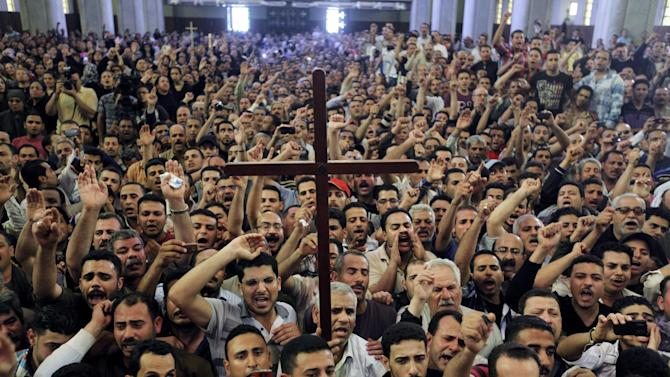 Egyptian Christians chant anti-Muslim Brotherhood slogans during a funeral service, at the Saint Mark Coptic cathedral in Cairo, Egypt, Sunday, April 7, 2013. Several Egyptians including 4 Christians and a Muslim were killed in sectarian clashes before dawn in Qalubiya, just outside of Cairo on Saturday, April 6, 2013. (AP Photo/Amr Nabil)