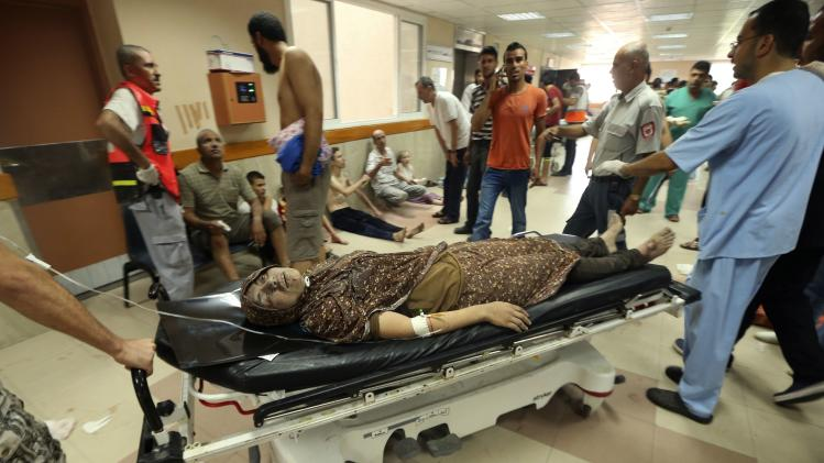 Palestinians wheel a woman, who medics said was wounded during heavy Israeli shelling, at a hospital in Gaza City