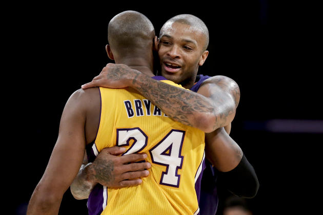 Phoenix Suns forward P.J. Tucker, right, hugs Los Angeles Lakers guard Kobe Bryant after an NBA basketball game in Los Angeles, Tuesday, Dec. 10, 2013