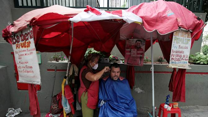 """A man gets his hair cut at a street barbershop decorated with a images of Venezuela's President Hugo Chavez in downtown Caracas,Venezuela, Tuesday, Dec. 11, 2012. Chavez was preparing to undergo a new cancer surgery on Tuesday in Cuba, his government said, after his illness reappeared despite a year and a half of surgeries and treatments. The Venezuelan president announced on Saturday that he needed to undergo a fourth cancer-related surgery after tests showed that """"some malignant cells"""" had reappeared in the same area in his pelvic region where tumors were previously removed. (AP Photo/Fernando Llano)"""