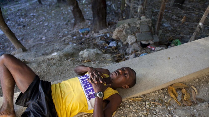 In this Jan. 7, 2013 photo, Astrel Clovis, a 42-year-old marathon runner, stretches his leg muscles outside his home in Petionville, a suburb of Port-au-Prince, Haiti.  Like virtually all Haitians in the capital of 3 million, the runner's life was disrupted by the catastrophic earthquake on Jan. 12, 2010.  Before the quake, he shared a three-bedroom house with his aunt and cousins, and dreamed of running his first marathon. The quake destroyed that house, along with about 100,000 homes across the capital and southern Haiti. The government put the death toll at 316,000, but no one knows how many people died. Clovis was lucky. He didn't lose any relatives, or close friends  - or his marathon dreams. (AP Photo/Dieu Nalio Chery)