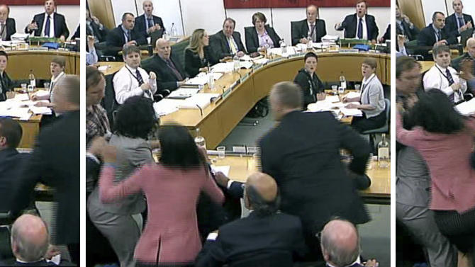 In this combo made from images taken from video, committee members and Wendi Deng, wife of Rupert Murdoch, foreground left, react as a protestor, at left in checked shirt , tries to throw a paper plate covered in shaving foam over Rupert Murdoch as he gives evidence to a House of Commons Committee on the News of the World phone hacking scandal in London, Tuesday, July 19, 2011. Video of 42-year-old Deng jumping forward to smack a protester with a pie aimed at Murdoch's face quickly went viral, and numerous fan pages quickly popped up on social networking sites such as Facebook praising her quick rapid reflexes. (AP Photo/Bowtie TV via APTN) UNITED KINGDOM OUT, NO SALES, NO ARCHIVE
