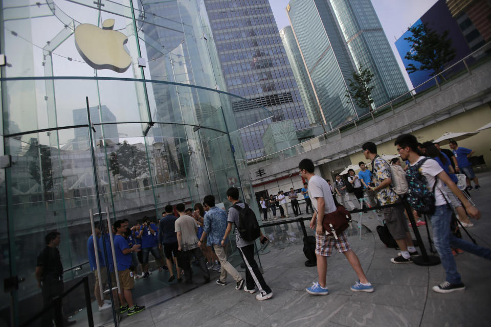Customers walk in an Apple Store to purchase new iPad tablet computers Friday, July 20, 2012 in Shanghai, China. (AP Photo/Eugene Hoshiko)