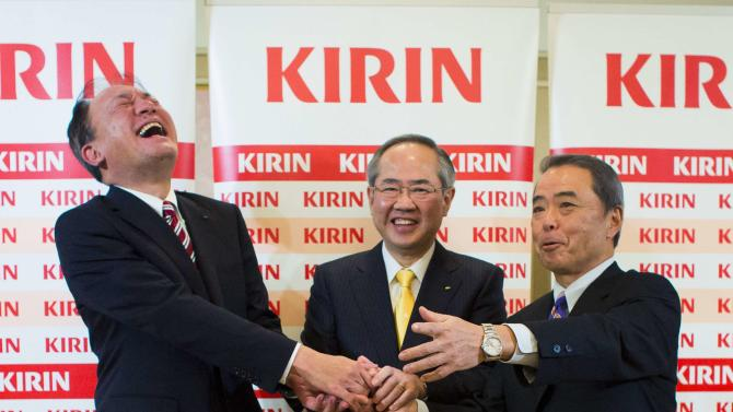 Upcoming President and CEO of Kirin Holdings Isozaki, his predecessor Miyake and the upcoming President of Kirin Brewery Fuse shake hands after a news conference in Tokyo
