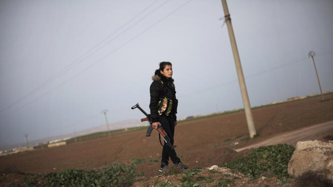FILE - In this Sunday, March. 3, 2013 file photo, A Kurdish female member of the Popular Protection Units stands guard at a check point near the northeastern city of Qamishli, Syria. Syria's Kurds have dramatically strengthened their hold on the far northeast reaches of the country, carving out territory as they drive out Islamic militant fighters allied to the rebellion and declaring their own civil administration in areas under their control this week amid the chaos of the civil war. The moves could be a first step toward creating an autonomous region similar to one Kurds run across the border as virtually a separate country within Iraq. But the Kurds' drive has angered rebels fighting to topple Syrian President Bashar Assad. It even worries some Kurds, who suspect the main faction leading the fighting and the new administration is actually acting on behalf of Assad to undermine the rebellion.(AP Photo/Manu Brabo, File)