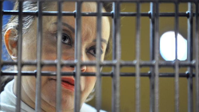 In this photo released by Mexico's federal court system, the head of Mexico's powerful teachers' union, Elba Esther Gordillo, stands behind bars as she appears for a hearing at a federal prison in Mexico City, Wednesday, Feb. 27, 2013. Mexico's most powerful woman was formally charged with a massive embezzlement scheme on Wednesday, standing grim-faced behind bars live on national television in what many called a clear message that the new government is asserting its authority. (AP Photo/Juzgado Sexto de Distrito en Procesos Penales Federales)