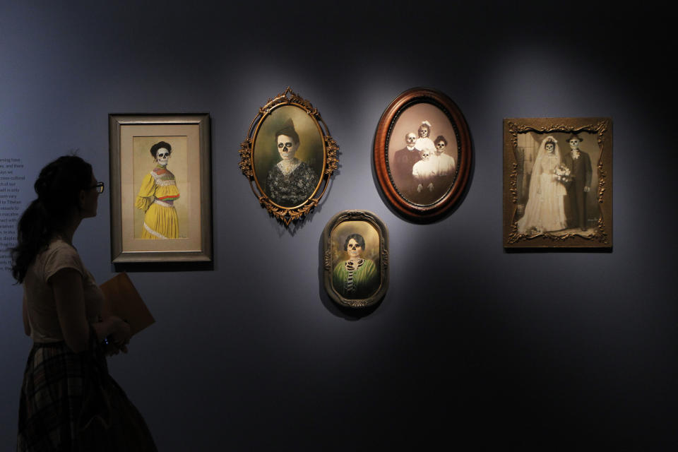 A visitor looks at family portraits by Mexican artist Marcos Raya on display at an exhibition 'Death : The Richard Harris Collection' at the Wellcome Collection gallery in London, Wednesday, Nov. 14, 2012. (AP Photo/Sang Tan)
