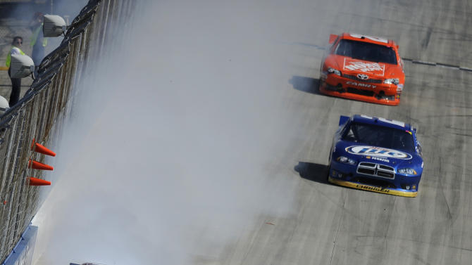 Smoke pours from the Jeff Burton's car, left, during the NASCAR Sprint Cup Series FedEx 400 auto race, Sunday, June 3, 2012, in Dover, Del. Also seen at right from front to rear are the cars of Greg Biffle, Marcos Ambrose, Brad Keselowski and Joey Logano. (AP Photo/Nick Wass)