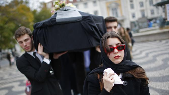 Students participate in a mock funeral march in Lisbon
