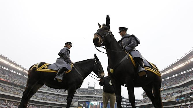 Army Cadets Katherine Deaton, left, atop Ranger 3 and Nels Estvold atop Stryker wait for the start an NCAA college football game against Navy, Saturday, Dec. 8, 2012, in Philadelphia. (AP Photo/Matt Rourke)