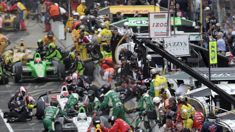 Teams, including those of Australia's Will Power (12) and Brazil's Helio Castroneves (3), pit during a yellow flag on lap 58 of the Indianapolis 500 auto race at Indianapolis Motor Speedway in Indianapolis, Sunday, May 26, 2013. (AP Photo/AJ Mast)