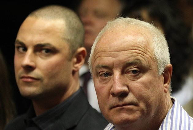 Olympic athlete Oscar Pistorius' father Henke Pistorius, right, with his son Carl watch as Oscar Pistorius walks in during his bail hearing at the magistrate court in Pretoria, South Africa, Friday, F