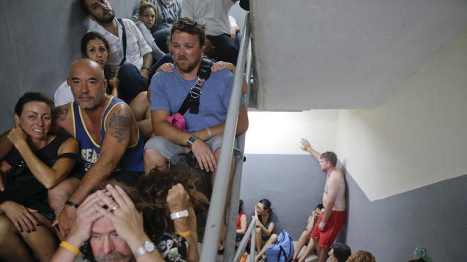 In this Sept. 15, 2014 photo, tourists sit on the concrete stairs in the service area of a resort after the designated area for shelter was destroyed by winds in Los Cabos, Mexico. Hurricane Odile raked the Baja California Peninsula with strong winds and heavy rains as locals and tourists in the resort area of Los Cabos began to emerge from shelters and assess the damage. (AP Photo/Victor R. Caivano)