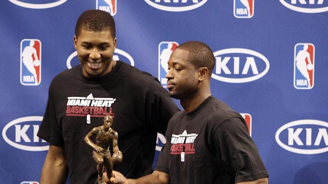 """Miami Heat guard Dwyane Wade, right, jokingly grabs LeBron James' NBA MVP trophy as he and teammate Dexter Pittman leave the stage after a ceremony to present the award to James, Saturday, May 12, 2012 in Miami. Calling the honor """"overwhelming"""" but pointing to a """"bigger goal,"""" James on Saturday became the eighth player in NBA history to win the MVP award three times. (AP Photo/Wilfredo Lee)"""