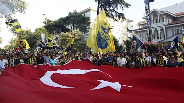 Fenerbahce supporters march to protest UEFA's decision to ban their club from European football (Reuters)