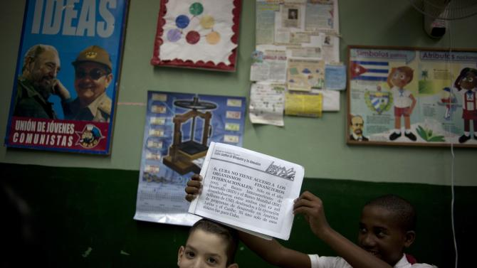Alejandro Josmel Predroso, right, jokingly holds up his homework, about the embargo against Cuba, over his friend's head during class at the Angela Landa elementary school in Old Havana, Cuba, Tuesday, Nov. 13, 2012. The U.N. General Assembly on Tuesday voted overwhelmingly to condemn the U.S. commercial, economic and financial embargo against Cuba for the 21st year in a row. The embargo was first enacted in 1960 following Cuba's nationalization of properties belonging to U.S. citizens and corporations. (AP Photo/Ramon Espinosa)