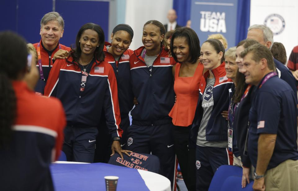 First lady Michelle Obama poses for a photo with members of the women's basketball team after speaking at a breakfast with Team USA at the 2012 Summer Olympics, Friday, July 27, 2012, in London. (AP Photo/Darron Cummings)