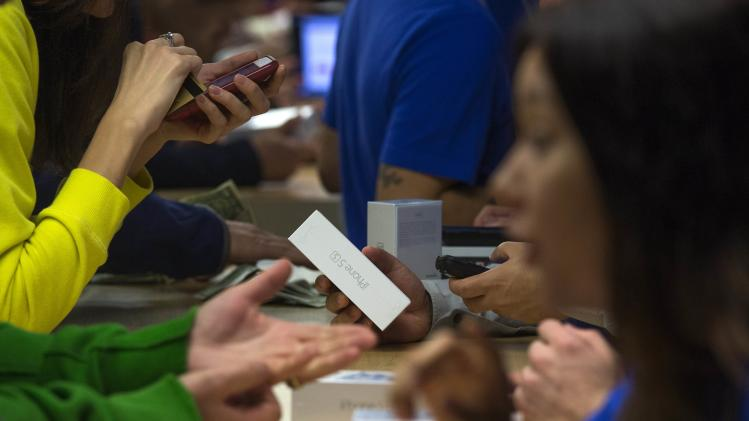 Customers purchase the iPhone 5s at the Apple retail store on Fifth Avenue in Manhattan, New York