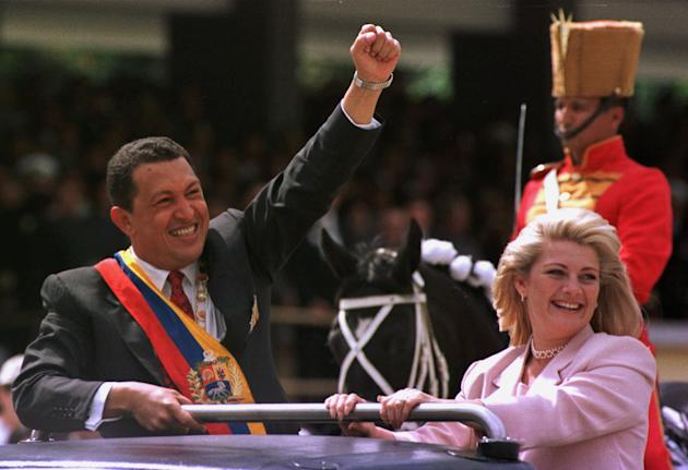 In this Feb. 4, 1999 file photo, Venezuela's newly sworn in President Hugo Chavez salutes the crowd next to his wife Marisabel Chavez during a military parade commemorating the seventh anniversary