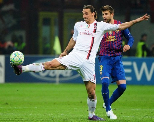 AC Milan's Zlatan Ibrahimovic (L) reaches out for the ball to head off Barcelona's Gerard Pique