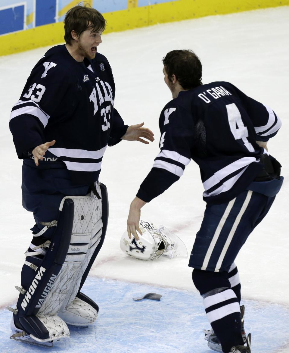 Yale goalie Jeff Malcolm (33) begins to celebrate with Rob O'Gara (4) after shutting out Quinnipiac 4-0 to win the NCAA men's college hockey Frozen Four national championship game in Pittsburgh, Saturday, April 13, 2013. (AP Photo/Gene Puskar)