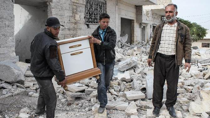 In this Saturday, Nov. 17, 2012 photo, a Syrian father and two of his sons salvage furniture from their home that was destroyed in bombing by government forces, in the northwestern city of Maraat al-Numan, Syria. After months of fierce fighting for control of the vital Aleppo-Damascus highway, rebels have succeeded in pushing the Syrian army out of the center of Maraat al-Numan located on the highway between Aleppo and Hama. (AP Photo/Mustafa Karali)