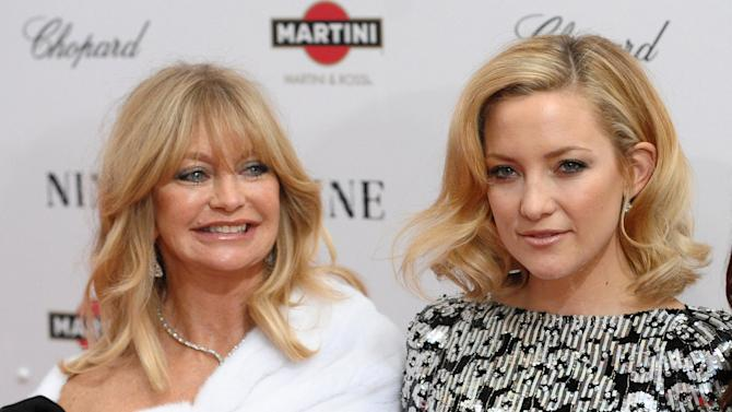 """FILE - This Dec. 15, 2009 file photo shows actress Goldie Hawn, left, and her daughter Kate Hudson at the premiere of """"Nine"""" at the Ziegfeld Theatre in New York. When Kate Hudson first burst onto the scene with the movie """"Almost Famous,"""" her uncanny resemblance to her mother Goldie Hawn had everybody talking. Hudson didn't see it. But now that she's a mother herself, the 34-year-old actress says she treasures the comparison. The mother-daughter pair has never acted together, but they teamed up for an Almay ad for Mother's Day.  (AP Photo/Peter Kramer, file)"""