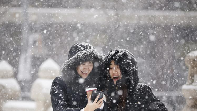 Women smile as they look at a picture on a mobile phone during snowfall in winter in central Seoul