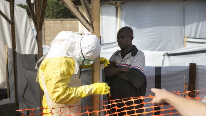 A health worker in protective gear receives a new suspected Ebola patient in a quarantine zone in a Red Cross facility in the town of Koidu