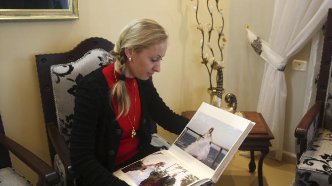 In this Wednesday, Feb. 20, 2013 photo, Ukrainian Alla Evdokimova, 26, who now goes by name Alaa Altif, displays her wedding album at her home at Mount Gerizim, near the West Bank town of Nablus. Alia emigrated to the West Bank and married Samaritan, Azzam Altif. The Samaritans, a rapidly dwindling sect dating to biblical times, have opened their insular community to brides imported from eastern Europe in a desperate quest to preserve their ancient culture. (AP Photo/Nasser Ishtayeh)