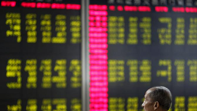 An investor watches an electronic board showing stock information at a brokerage office in Beijing