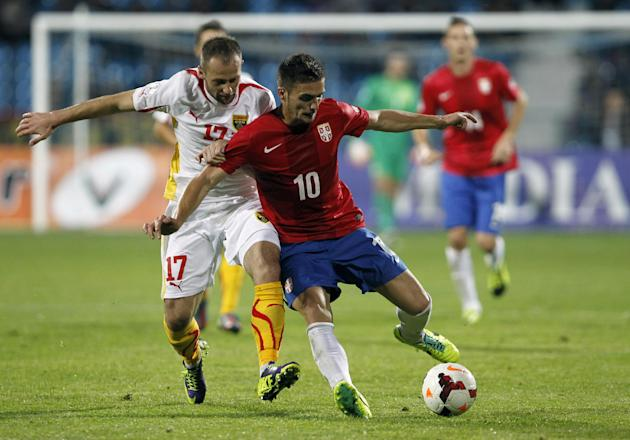 Serbia's Dusan Tadic, right, challenges for the ball with Macedonia's Ostoja Stjepanovic during their World Cup 2014 Group A qualifying soccer match at the City Stadium in Jagodina, Serbia, Tuesday, O
