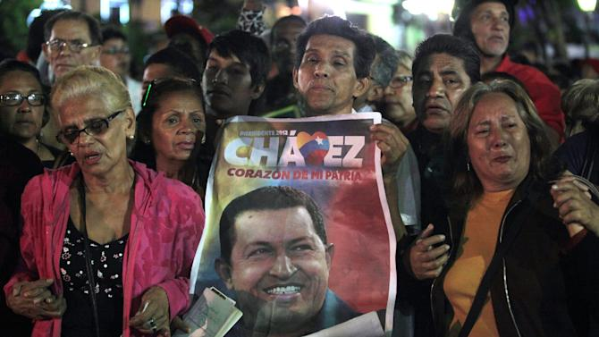People, one holding an image of Venezuela's President Hugo Chavez, gather to pray for him at Simon Bolivar square in Caracas, Venezuela, Tuesday, Dec. 11, 2012. Doctors began operating on Chavez in Cuba, his government said, after his cancer reappeared despite a year and a half of surgeries and treatments. (AP Photo/Fernando Llano)