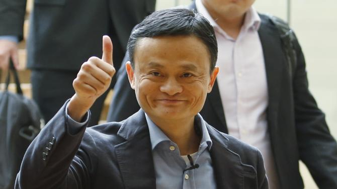 Alibaba founder Jack Ma gives a thumbs-up as he arrives to speak to investors at an initial public offering roadshow in Singapore