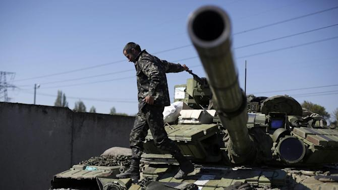 A Ukrainian serviceman is pictured on the top of an armoured personnel carrier, near the eastern town of Gorlivka in the Donetsk district on September 18, 2014